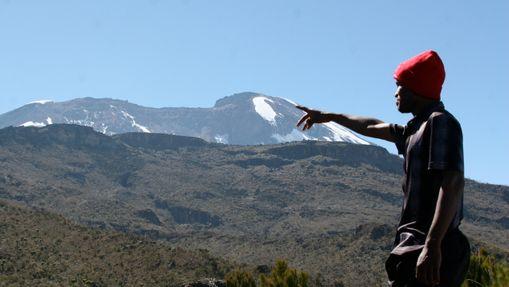 Porteur pointant le sommet du Kilimandjaro