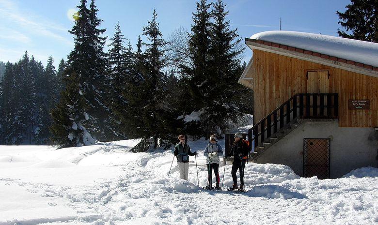 3 randonneurs en raquettes à côté d'un refuge