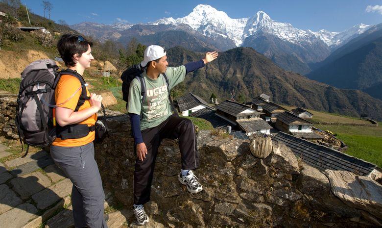 Guide népalais montrant un sommet à un trekkeur