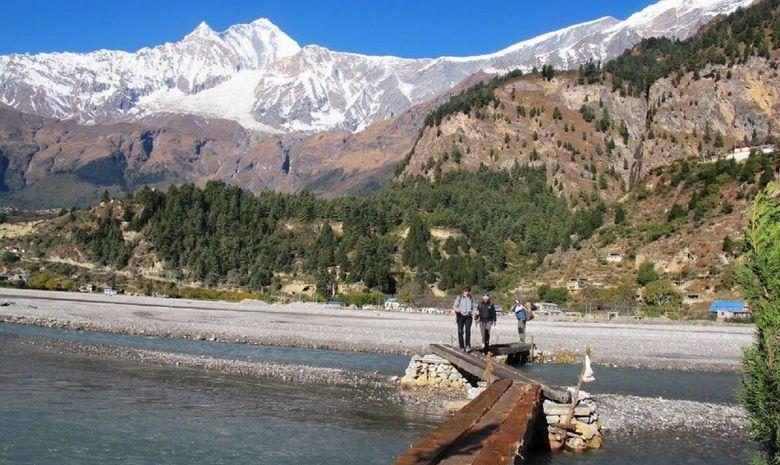 Trekkeur traversant une rivière vers Larjung
