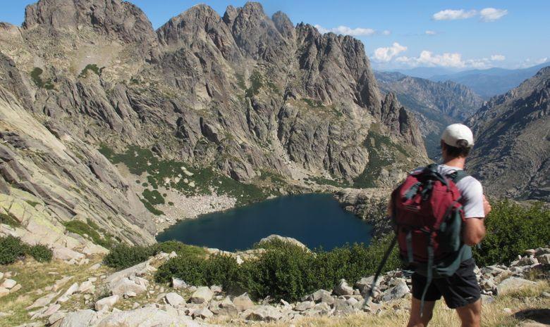 Randonneur devant un lac + vallée au loin